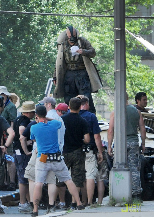 The Dark Knight Rises set photos from location shooting in Pittsburgh.  This candid shot of Tom Hardy as Bane reveals his full costume.